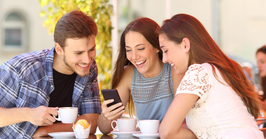 Three young people watching video on mobile device