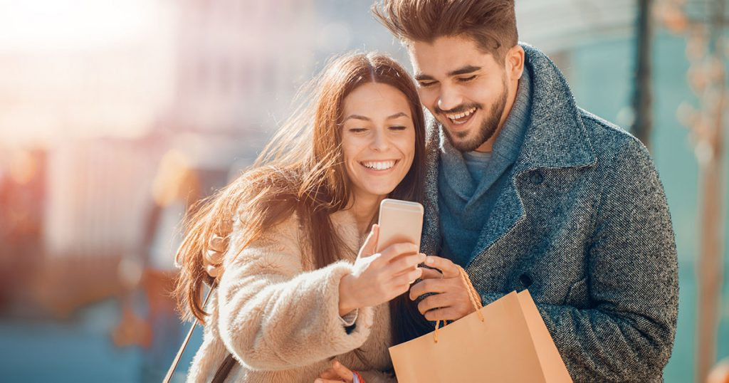 Man and woman looking at a phone while shopping together