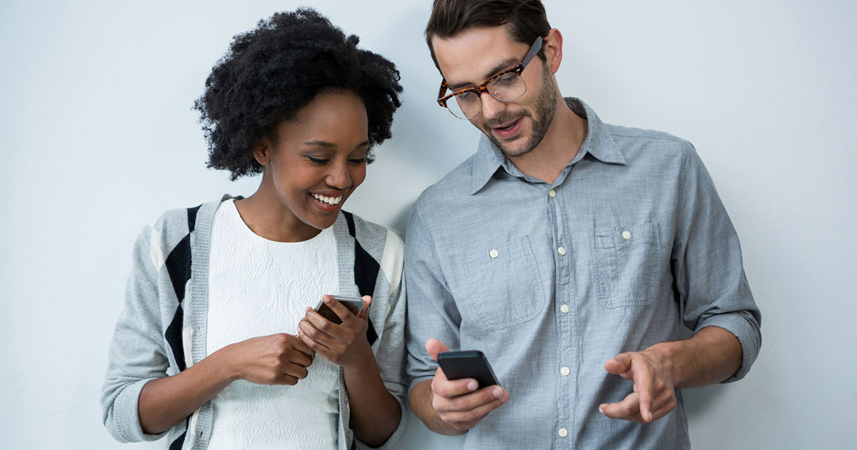 Man and woman standing against white wall using mobile phones