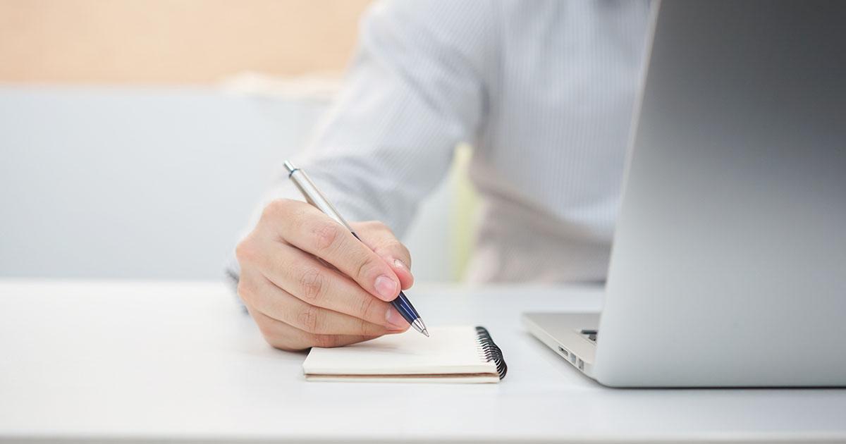 Businessman at laptop taking notes