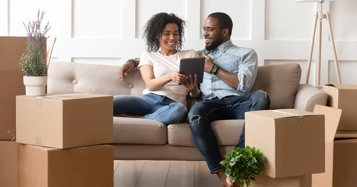 Man and woman use digital tablet on moving day