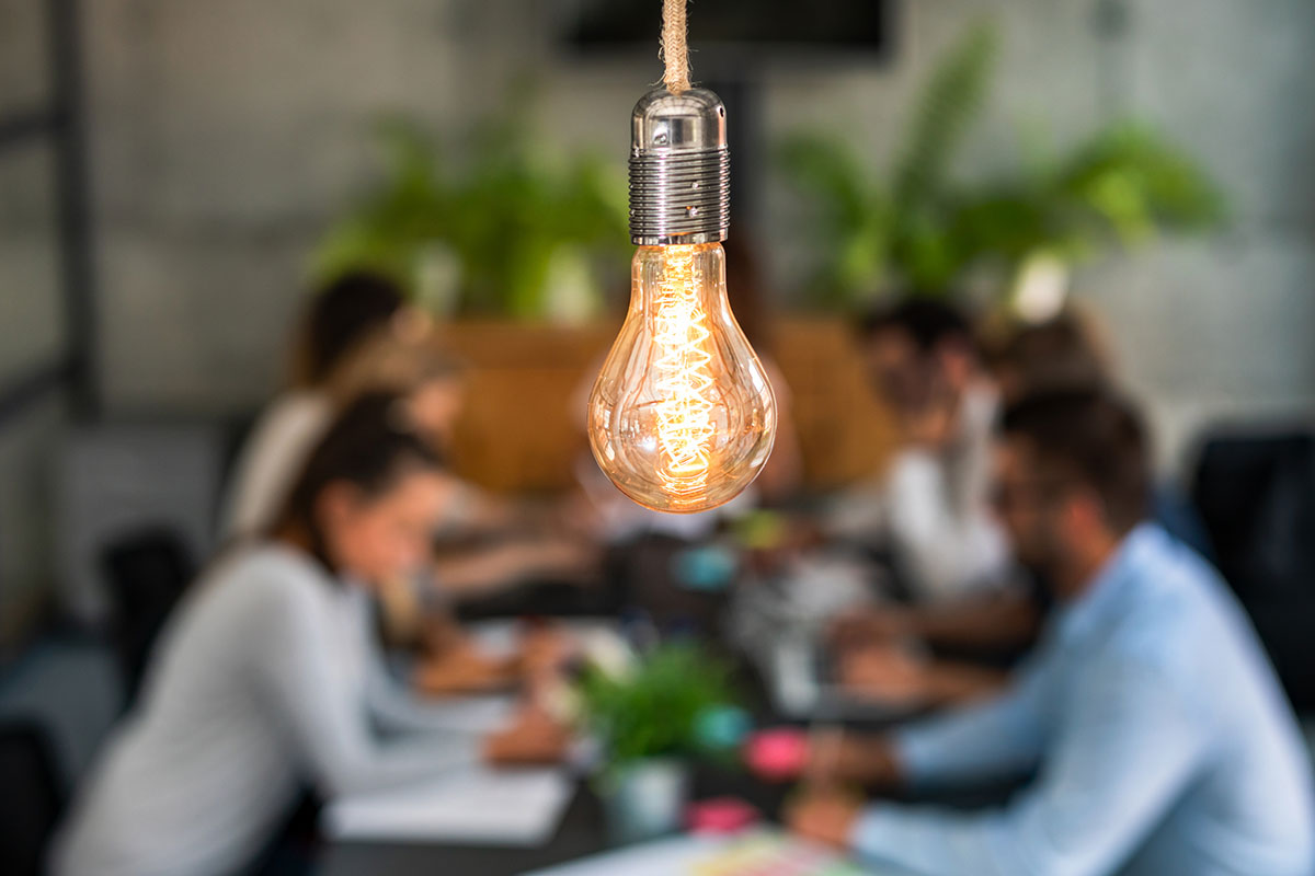 Light bulb with blurred creative team working in background