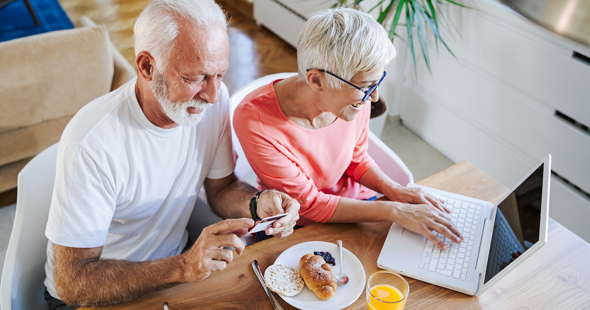 Boomer couple having breakfast, using laptop